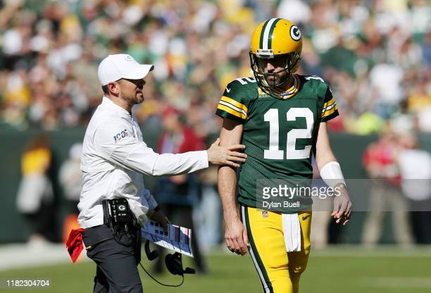 Head coach Matt LaFleur of the Green Bay Packers talks with Aaron Rodgers during the first half against the Oakland Raiders in the game at Lambeau...