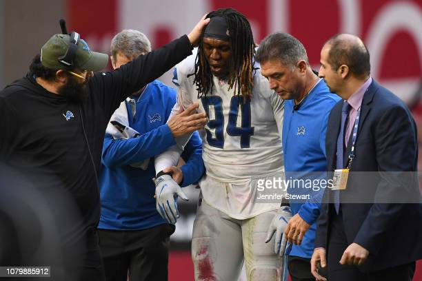 Head coach Matt Patricia of the Detroit Lions checks on Ezekiel Ansah after he was injured on a play in the first half of the NFL game against the...