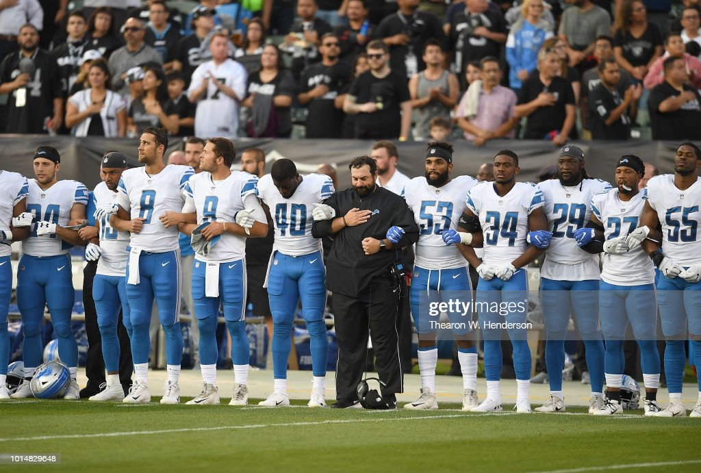 Head coach Matt Patricia of the Detroit Lions interlock arms with his players during the National Anthem prior to the start of an NFL preseason football game against the Oakland Athletics at Oakland Alameda Coliseum on August 10, 2018 in Oakland, California.