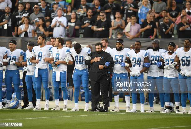 Head coach Matt Patricia of the Detroit Lions interlock arms with his players during the National Anthem prior to the start of an NFL preseason...