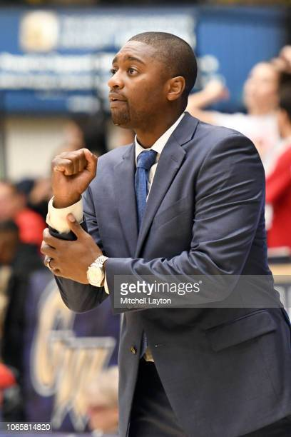 Head coach Maurice Joseph of the George Washington Colonials signals to his players during a college basketball game against the Stony Brook...