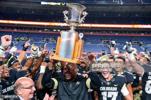 Head coach Mel Tucker of the Colorado Buffaloes lifts the Centennial Cup awarded to the winner of the annual rivalry game between the Colorado...