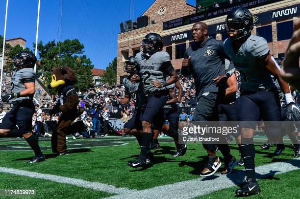 Head coach Mel Tucker of the Colorado Buffaloes runs onto the field with players before a game against the Air Force Falcons at Folsom Field on...