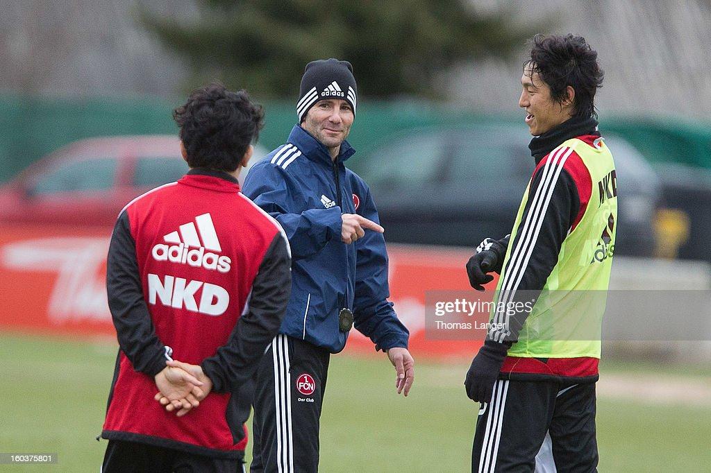 Head coach Michael Wiesinger speaks via interpreter Junpei Yamamori (L) with new player Mu Kanazaki (R) of 1 FC Nuernberg during a training session on January 30, 2013 at the Sportpark Valznerweiher in Nuremberg, Germany.