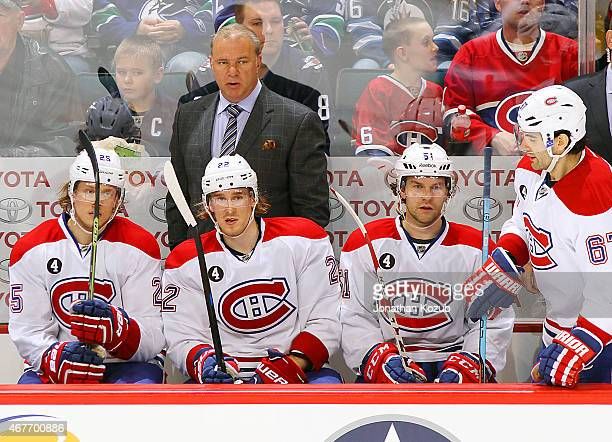 Head Coach Michel Therrien of the Montreal Canadiens looks on from the bench behind players Jacob De La Rose Dale Weise David Desharnais and Max...