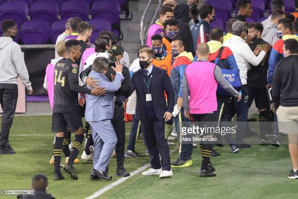 Head coach Miguel Herrera of Club America is restrained after a halftime scuffle during the CONCACAF Champions League semifinal game against the Los...