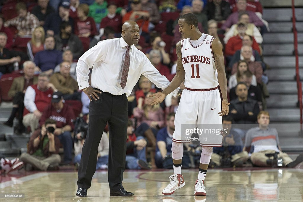 Head Coach Mike Anderson talks with BJ Young #11 of the Arkansas Razorbacks during a game against the Auburn Tigers at Bud Walton Arena on January 16, 2013 in Fayetteville, Arkansas. The Razorbacks defeated the Tigers 88-80.