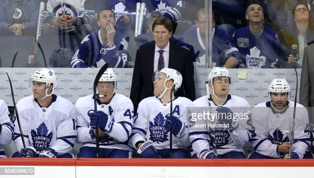 Head coach Mike Babcock of the Toronto Maple Leafs behind the bench during NHL action against the Winnipeg Jets on October 4 2017 at the Bell MTS...