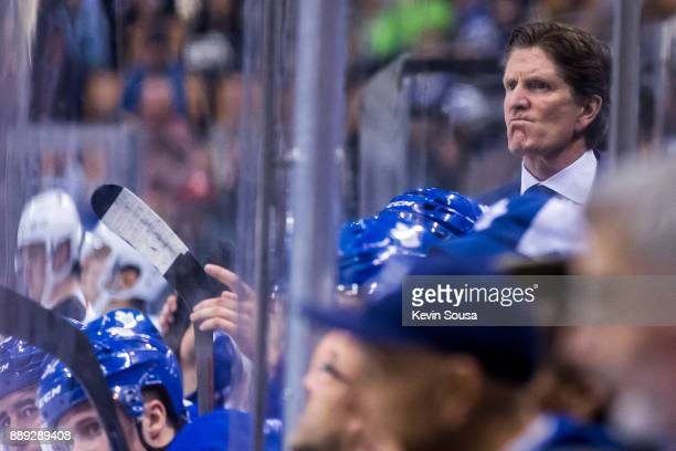 Head Coach Mike Babcock of the Toronto Maple Leafs watches from the bench during an NHL game against the Calgary Flames during the third period at...