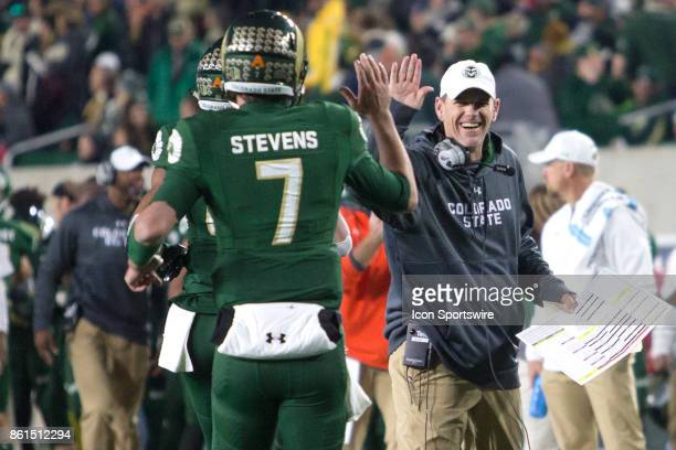 CSU head coach Mike Bobo high fives quarterback Nick Stevens during the UNR at CSU football game at Sonny Lubick Field at Hughes Stadium in Fort...