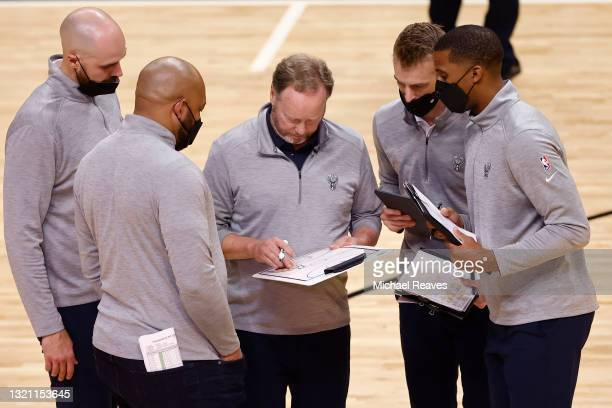 Head coach Mike Budenholzer of the Milwaukee Bucks talks with his assistant coaches against the Miami Heat during the fourth quarter in Game Three of...