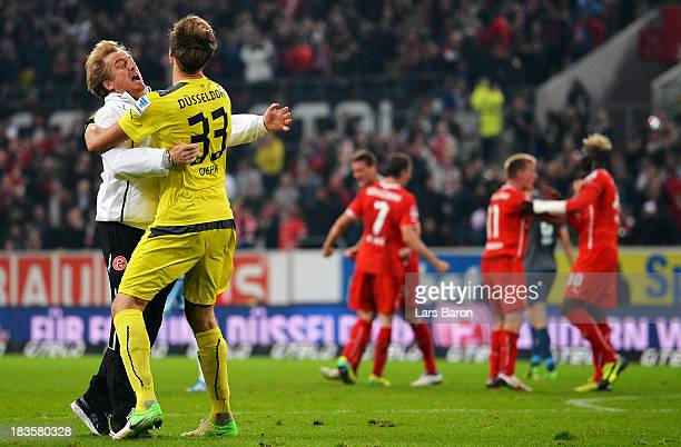 Head coach Mike Bueskens of Duesseldorf celebrates with goalkeeper Fabian Giefer after winning the Second Bundesliga match between Fortuna...