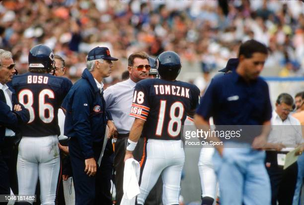 Head Coach Mike Ditka of the Chicago Bears talks with his quarterback Mike Tomczak during an NFL football game circa 1989 at Soldier Field in Chicago...