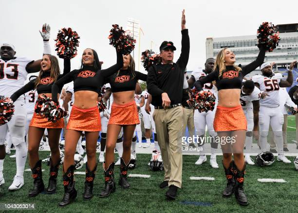 Head coach Mike Gundy of the Oklahoma State Cowboys celebrates with his team and cheerleaders after their 4828 win against the Kansas Jayhawks at...