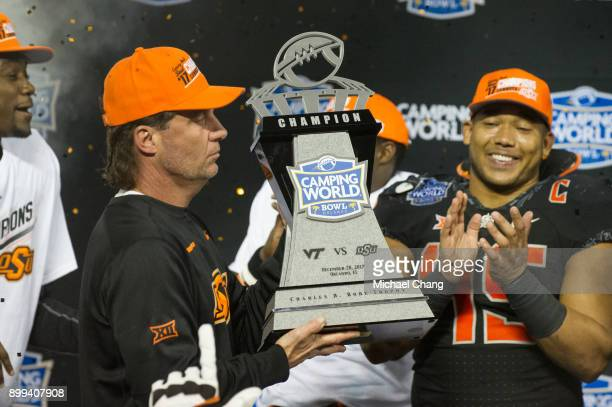 Head coach Mike Gundy of the Oklahoma State Cowboys holds the Camping World Bowl Trophy after defeating the Virginia Tech Hokies on December 28 2017...