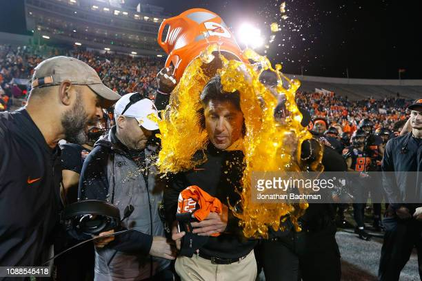 Head coach Mike Gundy of the Oklahoma State Cowboys is dunked with Gatorade after winning the AutoZone Liberty Bowl against the Missouri Tigers at...