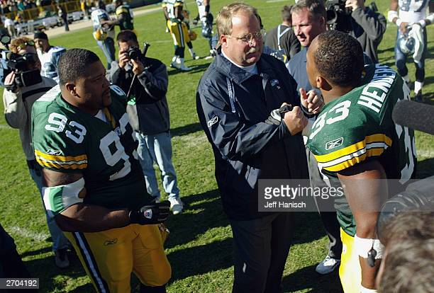 Head coach Mike Holmgren of the Seattle Seahawks greets fullback William Henderson and defensive tackle Gilbert Brown of the Green Bay Packers after...
