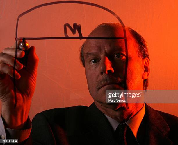 Head Coach Mike Keenan of the Calgary Flames draws out a play during a photo session in the first round of the 2007 NHL Entry Draft at Nationwide...