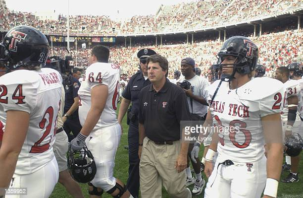 Head Coach Mike Leach of the Texas Tech Red Raiders walks on the field with his players after losing the NCAA Pigskin Classic against the Ohio State...