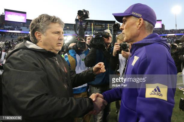 Head Coach Mike Leach of the Washington State Cougars and head coach Chris Petersen of the Washington Huskies shake hands after the Washington...