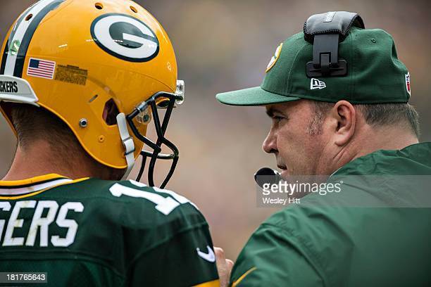 Head Coach Mike McCarthy and Aaron Rodgers of the Green Bay Packers talk on the field before a game against the Washington Redskins at Lambeau Field...