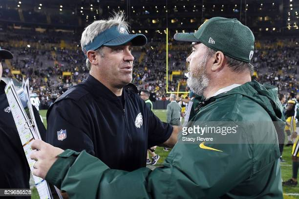 Head coach Mike McCarthy of the Green Bay Packers greets head coach Doug Pederson of the Philadelphia Eagles at midfield following a prseason game at...