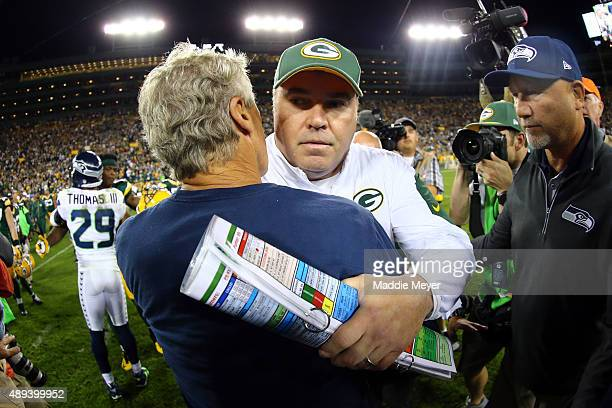 Head coach Mike McCarthy of the Green Bay Packers hugs head coach Pete Carroll of the Seattle Seahawks after their game at Lambeau Field on September...