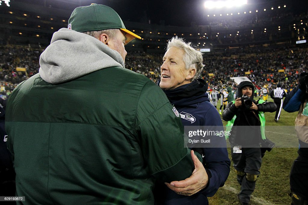 Head coach Mike McCarthy of the Green Bay Packers (L) meets with head coach Pete Carroll of the Seattle Seahawks after the Green Bay Packers beat the Seattle Seahawks 38-10 at Lambeau Field on December 11, 2016 in Green Bay, Wisconsin.