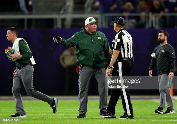 Head coach Mike McCarthy of the Green Bay Packers speaks with line judge Mark Perlman at US Bank Stadium on November 25 2018 in Minneapolis Minnesota