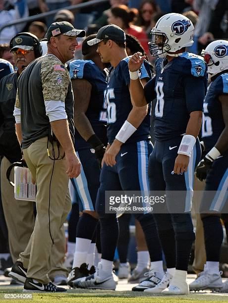Head coach Mike Mularkey of the Tennessee Titans speaks to quarterback Marcus Mariota after a touchdown during the first half of a game against the...