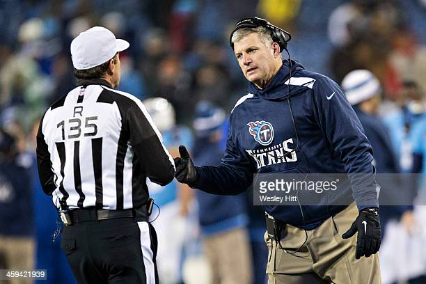 Head Coach Mike Munchak of the Tennessee Titans talks with Referee Pete Morelli during a game against the Arizona Cardinals at LP Field on December...
