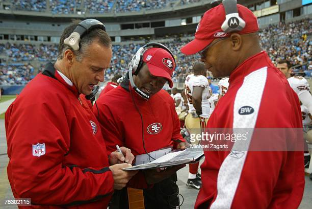 Head Coach Mike Nolan meets with Mike Singletary and Vance Joseph of the San Francisco 49ers during the NFL game against the Carolina Panthers at...