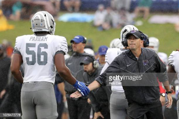 Head coach Mike Norvell of the Memphis Tigers congratulates Dylan Parham of the Memphis Tigers in the first half against the Navy Midshipmen at...