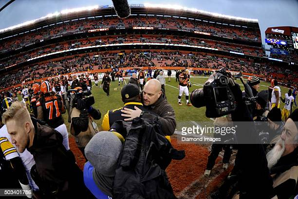 Head coach Mike Pettine of the Cleveland Browns embraces head coach Mike Tomlin of the Pittsburgh Steelers after a game on January 3 2016 at...