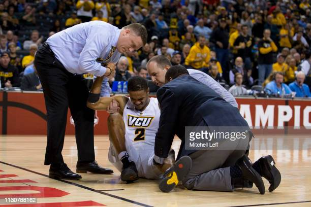 Head coach Mike Rhoades of the Virginia Commonwealth Rams helps Marcus Evans off the court after an injury against the Rhode Island Rams during the...