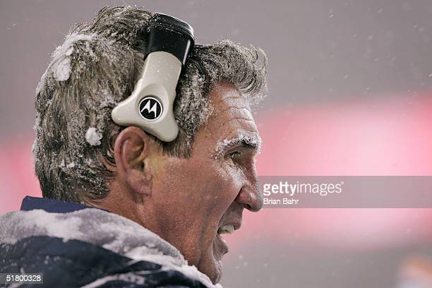 Head coach Mike Shanahan of the Denver Broncos coaches from the sidelines in the snow during the second half against the Oakland Raiders on November...