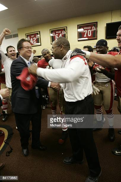 Head coach Mike Singletary of the San Francisco 49ers celebrates with Dr John York in the locker room after the NFL game against the Washington...