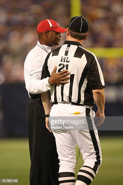 Head Coach Mike Singletary of the San Francisco 49ers confers with Head Linesman John Schleyer during the game against the Minnesota Vikings at...
