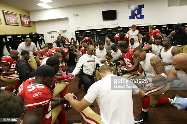 Head coach Mike Singletary of the San Francisco 49ers leads a team prayer in the locker room after the NFL game against the St Louis Rams at...