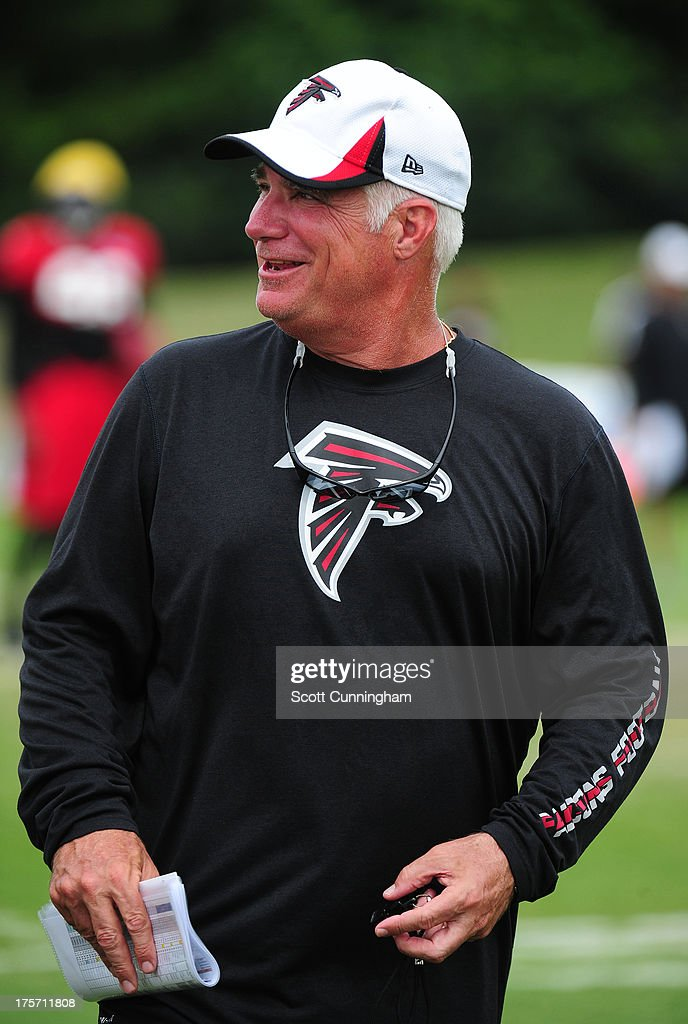 Head Coach Mike Smith of the Atlanta Falcons relaxes before practice against the Cincinnati Bengals at the Atlanta Falcons Training Complex on August 6 2013 in Flowery Branch, Georgia.