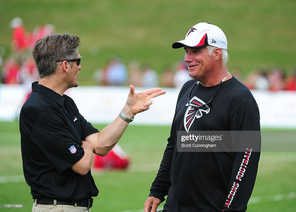 Head Coach Mike Smith (R) of the Atlanta Falcons speaks with General Manager Thomas Dimitroff during practice against the Cincinnati Bengals at the Atlanta Falcons Training Complex on August 6 2013 in Flowery Branch, Georgia.