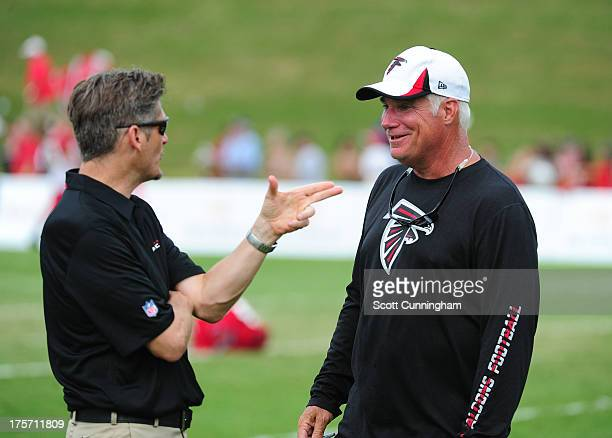 Head Coach Mike Smith of the Atlanta Falcons speaks with General Manager Thomas Dimitroff during practice against the Cincinnati Bengals at the...