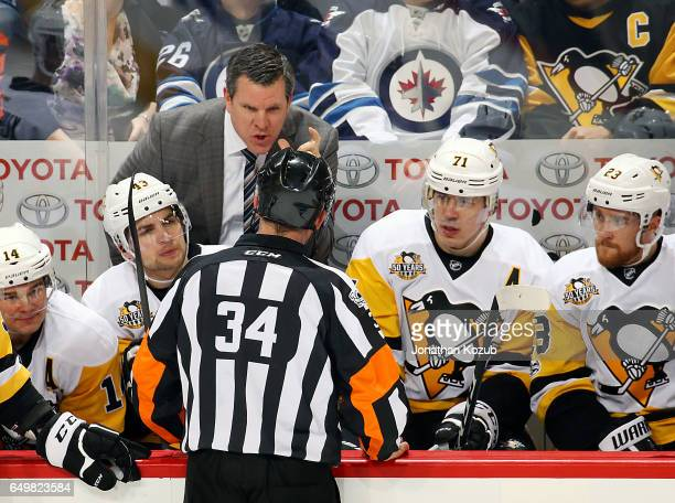 Head Coach Mike Sullivan of the Pittsburgh Penguins has words with referee Brad Meier during a first period stoppage in play against the Winnipeg...