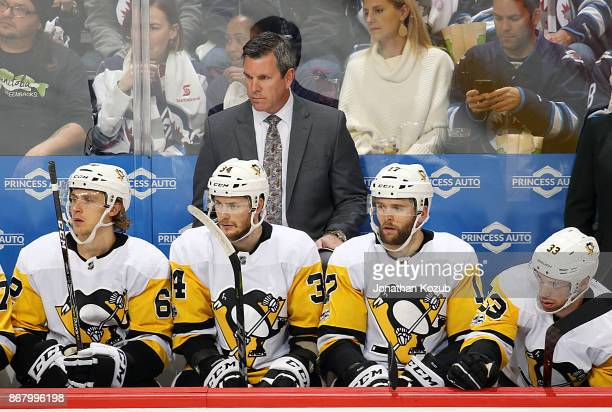 Head Coach Mike Sullivan of the Pittsburgh Penguins looks on from the bench during third period action against the Winnipeg Jets at the Bell MTS...