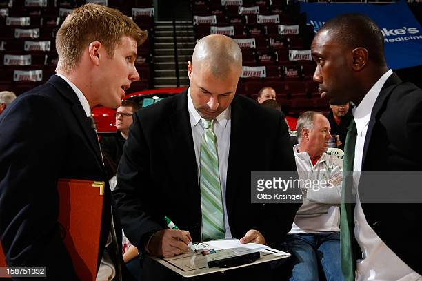 Head Coach Mike Taylor of the Maine Red Claws writes while Assistant Coaches JP Clark and Tunde Adekola talk during the NBA DLeague game against the...