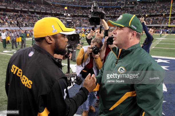 Head coach Mike Tomlin of the Pittsburgh Steelers and head coach Mike McCarthy of the Green Bay Packers speak prior to Super Bowl XLV at Cowboys...