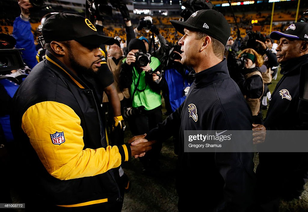 Head coach Mike Tomlin of the Pittsburgh Steelers meets head coach John Harbaugh of the Baltimore Ravens after the Ravens defeated the Steelers 30-17 in their AFC Wild Card game at Heinz Field on January 3, 2015 in Pittsburgh, Pennsylvania.