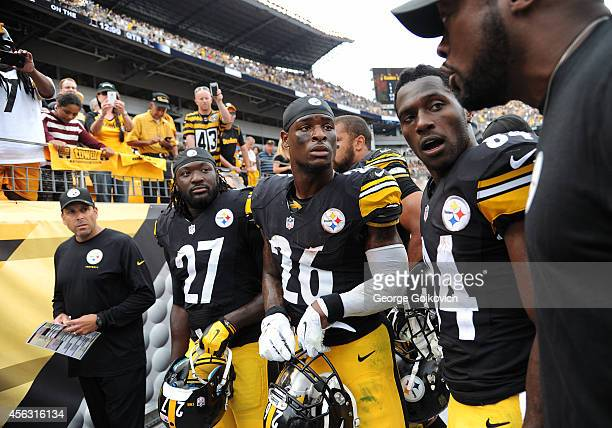 Head coach Mike Tomlin of the Pittsburgh Steelers talks to running backs LeGarrette Blount and Le'Veon Bell and wide receiver Antonio Brown as...