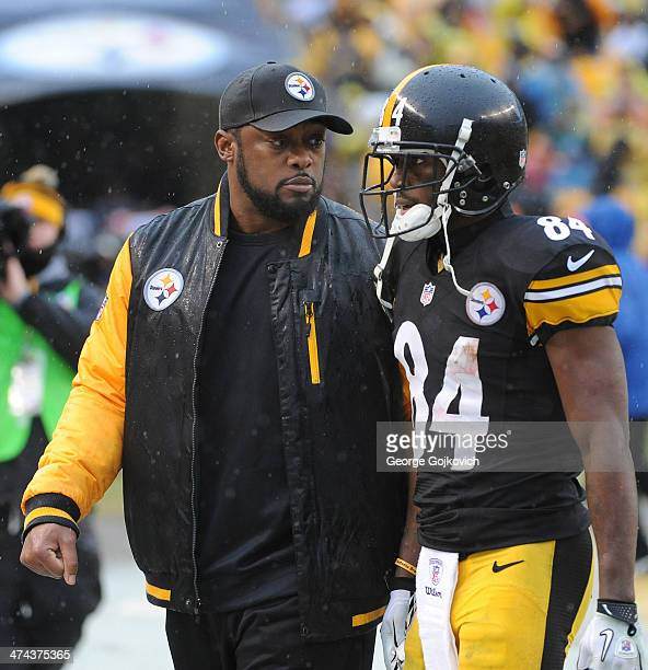 Head coach Mike Tomlin of the Pittsburgh Steelers talks to wide receiver Antonio Brown as they walk off the field at the end of the first half during...