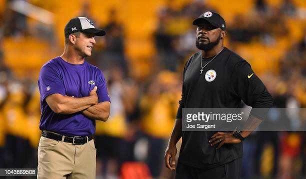 Head coach Mike Tomlin of the Pittsburgh Steelers talks with head coach John Harbaugh of the Baltimore Ravens during warmups before the game at Heinz...